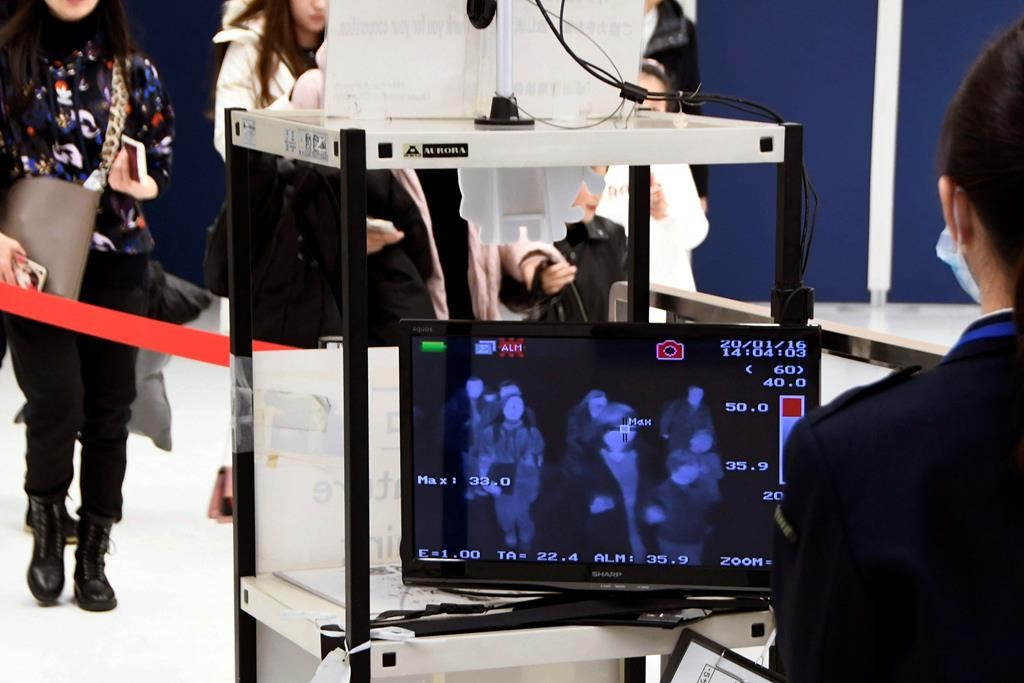 In this Jan. 16, 2020, photo, travelers from China's Wuhan go through body temperature scanners at Narita airport in Narita, near Tokyo. A fourth person has died in an outbreak of a new coronavirus in China, authorities said Tuesday, Jan. 21, 2020, as more places stepped up medical screening of travelers from the country as it enters its busiest travel period. (Kyodo News via AP).