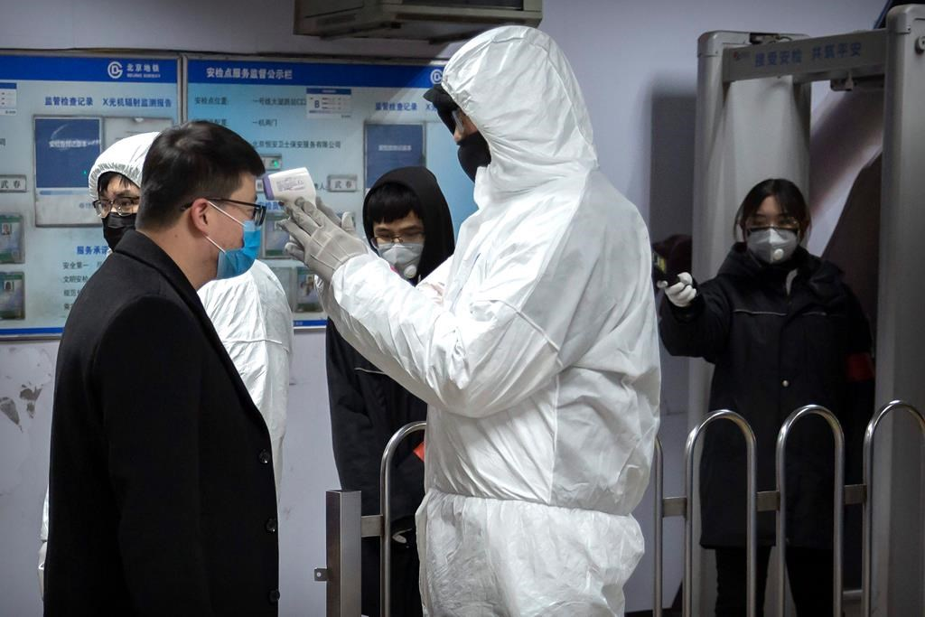 A worker wearing a hazardous materials suit takes the temperature of a passenger at the entrance to a subway station in Beijing, Sunday, Jan. 26, 2020. The new virus accelerated its spread in China, and the U.S. Consulate in the epicentre of the outbreak, the central city of Wuhan, announced Sunday it will evacuate its personnel and some private citizens aboard a charter flight.