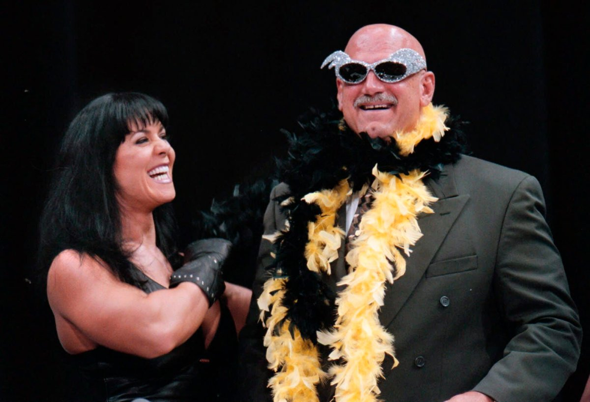FILE - In this July 14, 1999 file photo, Minnesota Gov. Jesse Ventura is adorned with his signature feather boa and glitter sunglasses by professional wrestler Chyna, during a World Wrestling Federation press conference at the Target Center in Minneapolis.