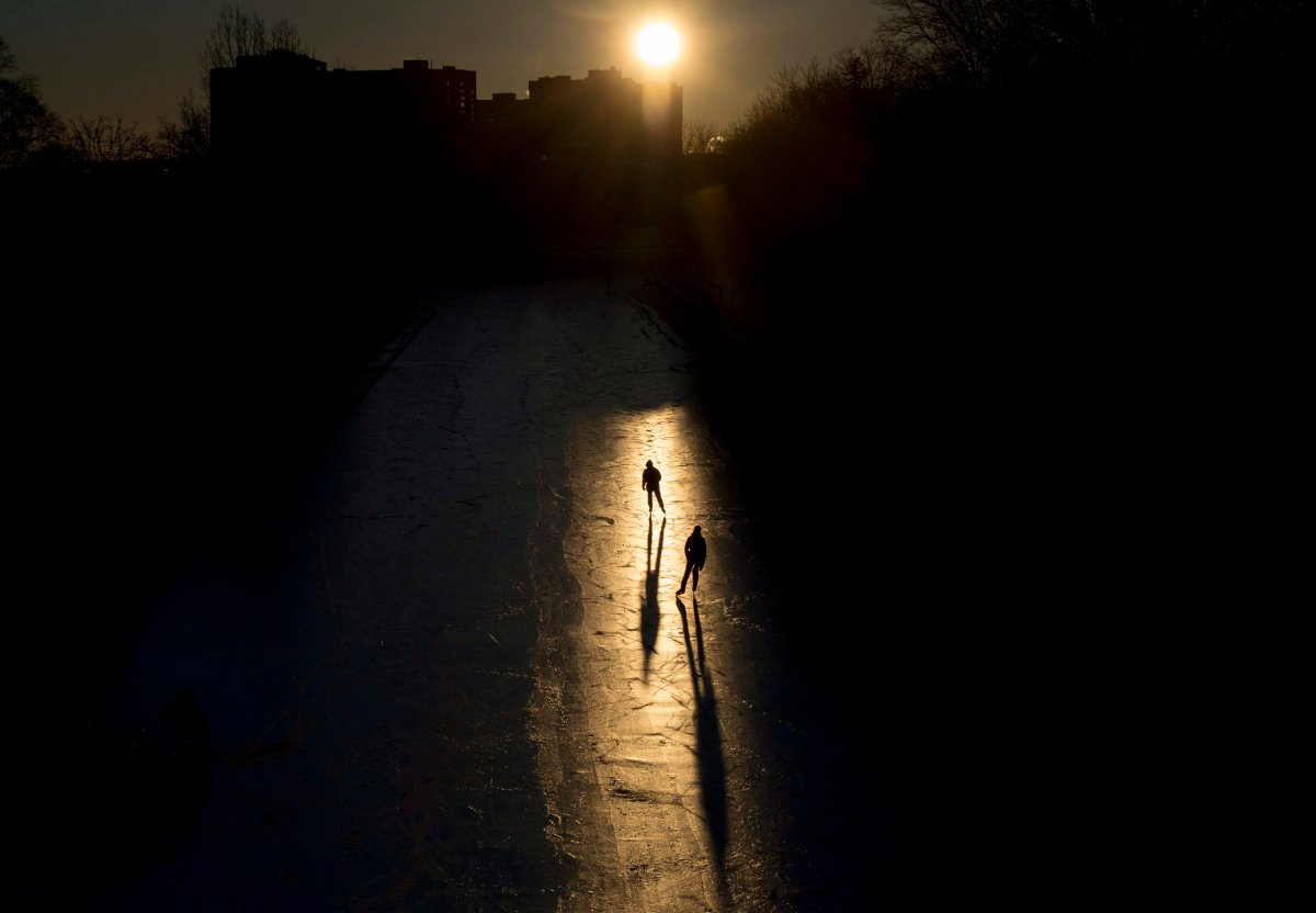 Skaters are silhouetted in a beam of sunlight as they make their way along the Rideau Canal Skateway shortly after dawn on Sunday, Jan. 15, 2017 in Ottawa.