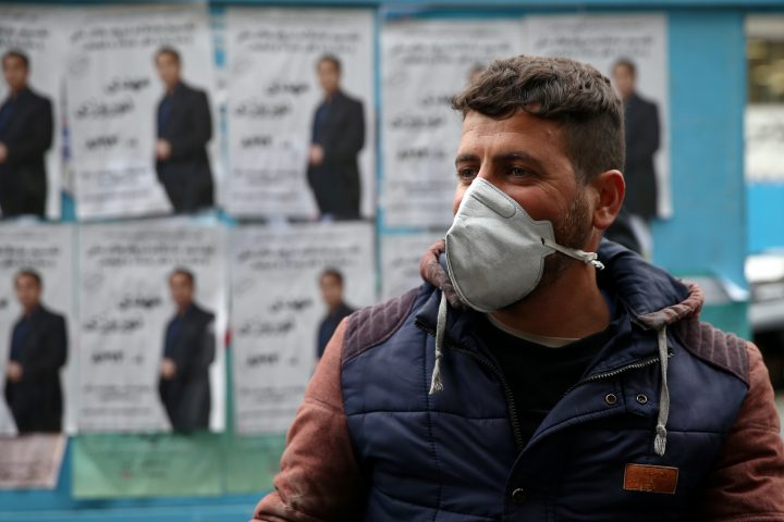 A man stands in front of parliamentary election campaign posters in Tehran, Iran, Feb. 20, 2020.