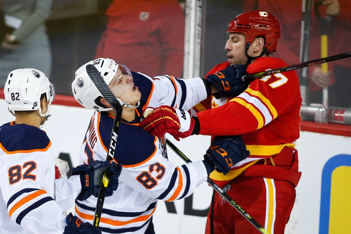 Edmonton Oilers' Matt Benning, left, and Calgary Flames' Milan Lucic scuffle during second period NHL hockey action in Calgary, Saturday, Feb. 1, 2020.THE CANADIAN PRESS/Jeff McIntosh.