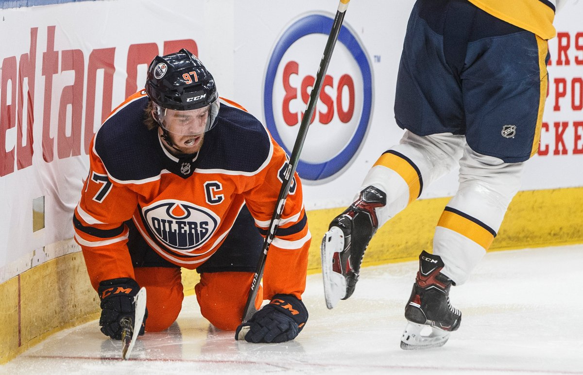 Edmonton Oilers' Connor McDavid (97) gets up slowly after going into the boards against the Nashville Predators during second period NHL action in Edmonton, Alta., on Saturday, February 8, 2020. Edmonton captain Connor McDavid will be out two to three weeks with a quad injury. THE CANADIAN PRESS/Jason Franson.