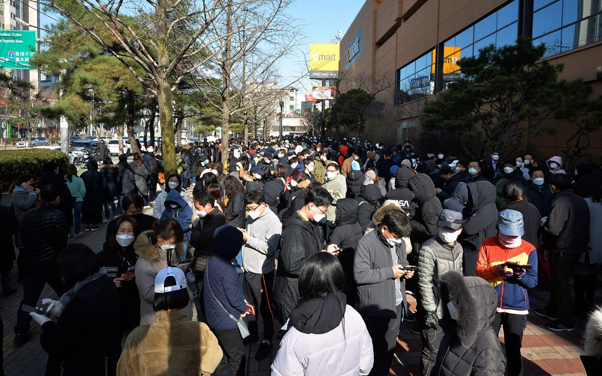 """People line up to buy face masks at a store in Daegu, South Korea, Monday, Feb. 24, 2020. South Korea's President Moon Jae-in on Sunday put the country on its highest alert for infectious diseases and says officials should take """"unprecedented, powerful"""" steps to fight a viral outbreak. (Lee Moo-ryul/Newsis via AP)."""