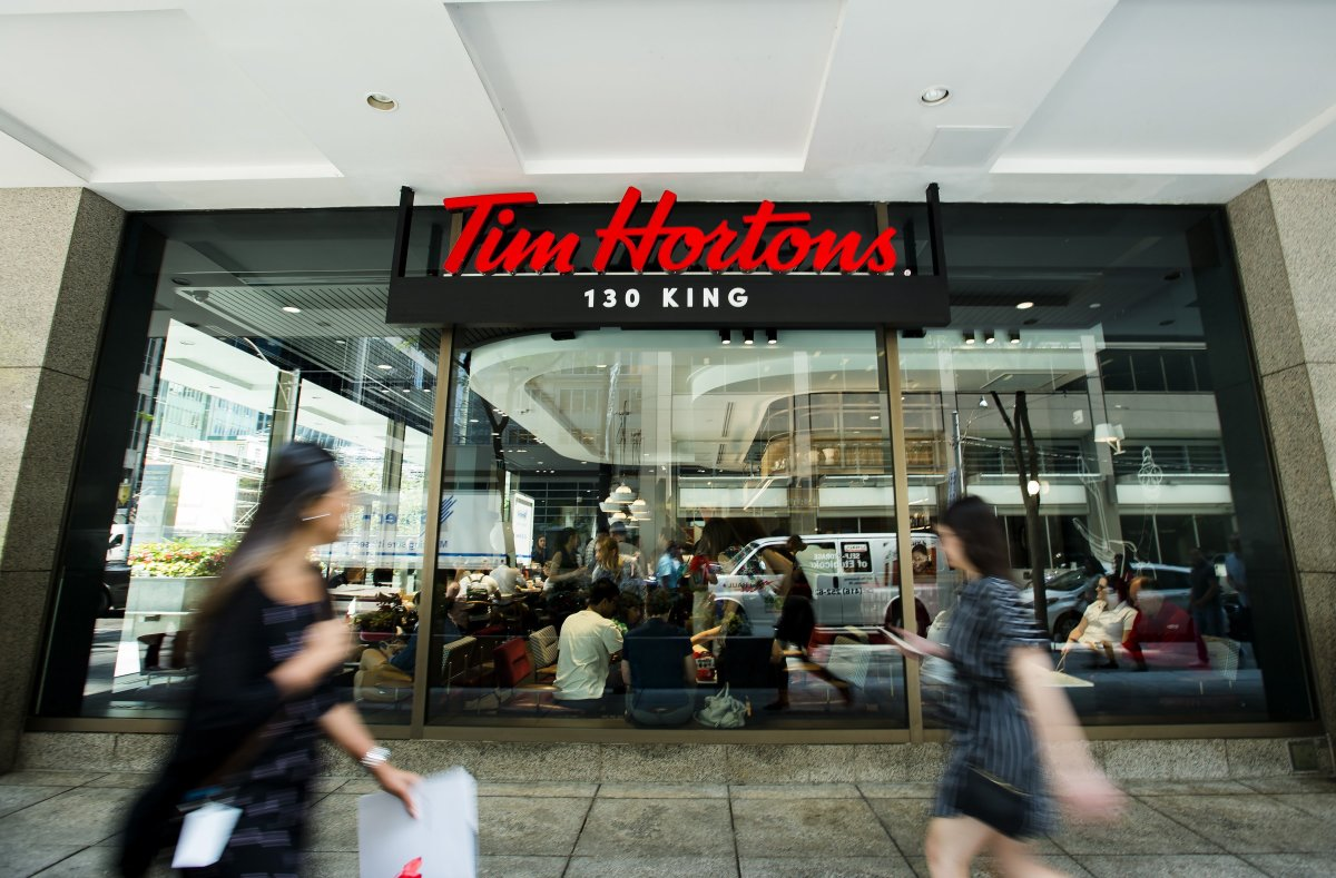 People walk past a newly renovated Tim Hortons in Toronto on Thursday, July 25, 2019.