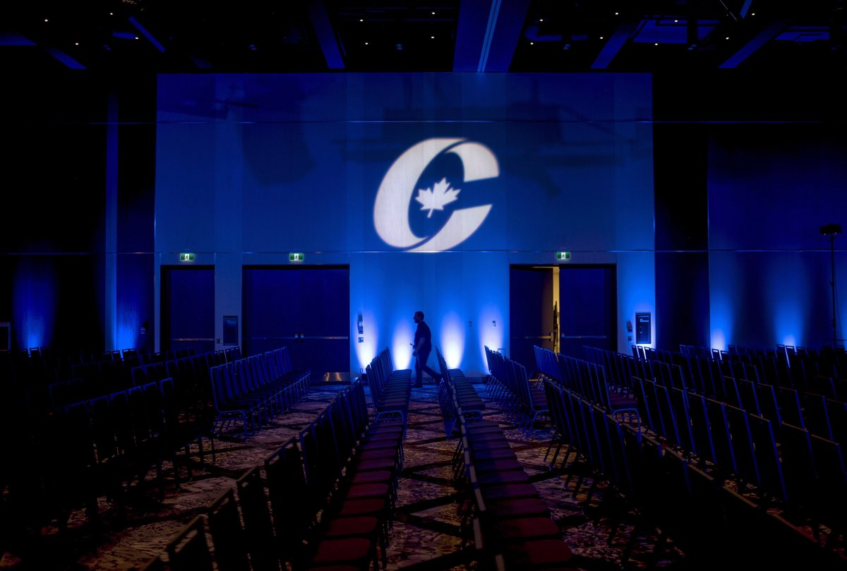 A man is silhouetted walking past a Conservative Party logo before the opening of the Party's national convention in Halifax on Thursday, August 23, 2018.