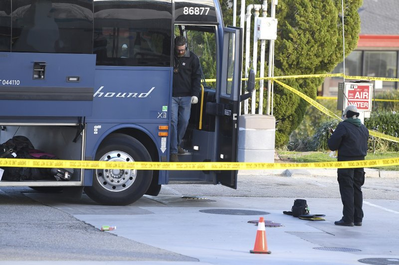 Investigators are seen outside of a Greyhound bus after a passenger was killed on board on Monday, Feb. 3, 2020 in Lebec, Calif.