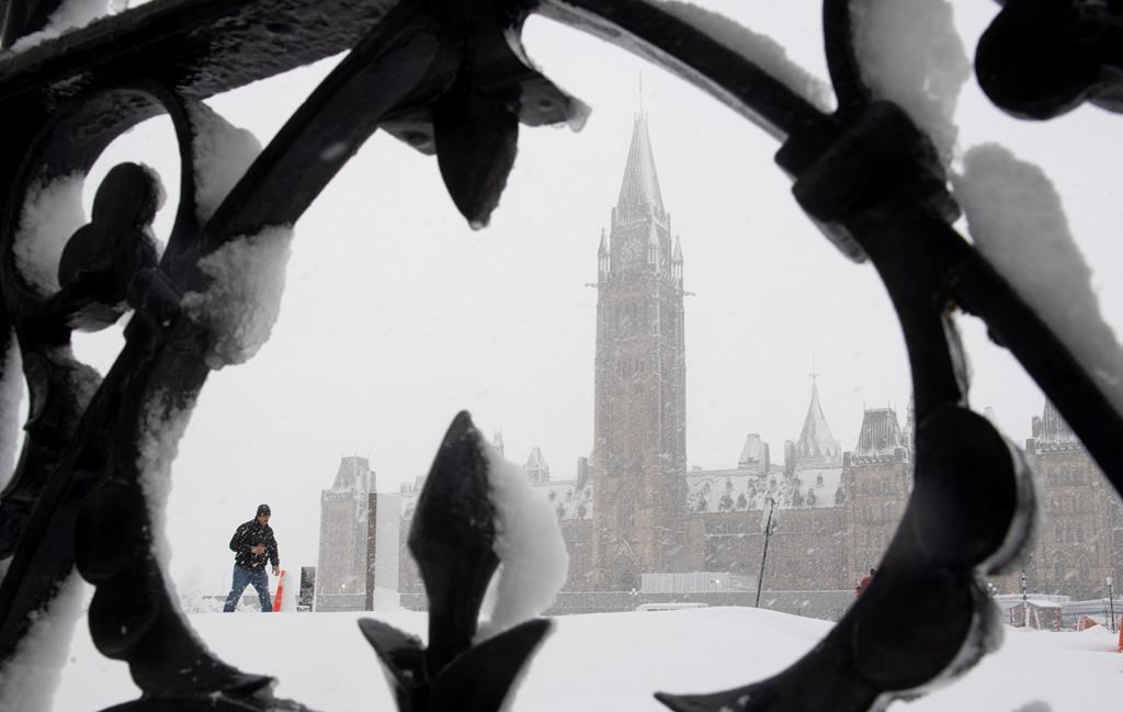 A man walks on Parliament Hill during a snow storm in Ottawa, Thursday, Feb. 27, 2020. Over 25cm of snow was expected to fall on the region as a winter storm passed through.