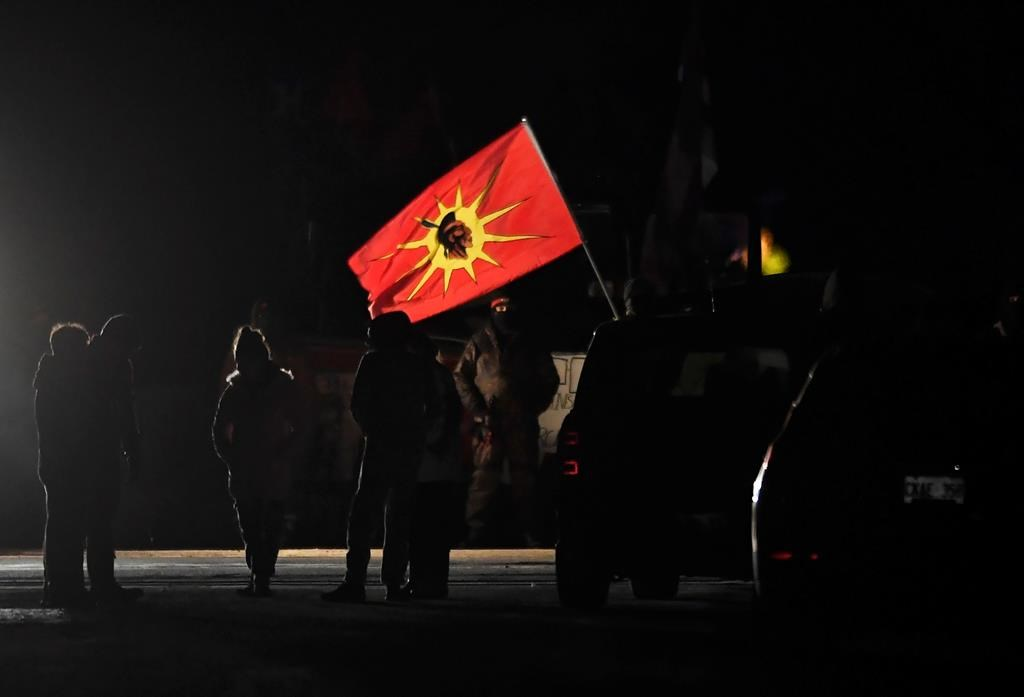 Protesters stand at a rail blockade in Tyendinaga Mohawk Territory, near Belleville, Ont., on Sunday Feb. 23, 2020, during a protest in solidarity with Wet'suwet'en Nation hereditary chiefs attempting to halt construction of a natural gas pipeline on their traditional territories.