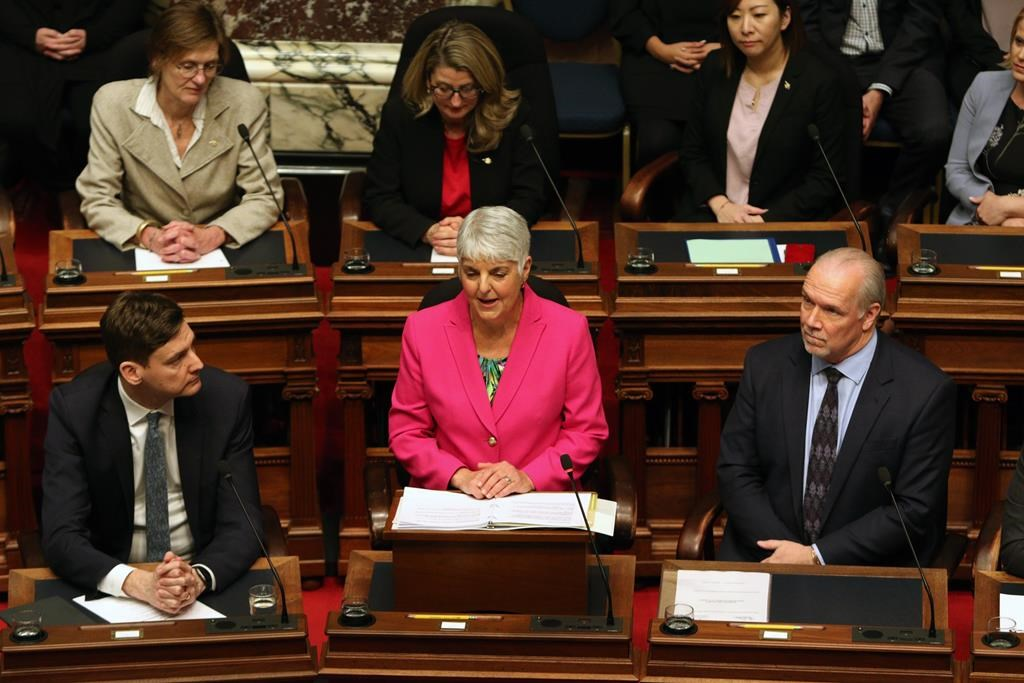 Attorney General David Eby and Premier John Horgan look on as Minister of Finance Carole James delivers the budget speech from the legislative assembly at B.C. Legislature in Victoria, B.C., on Tuesday, February 18, 2020.