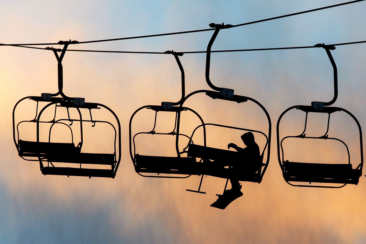 A silhouetted snowboarder makes his way up the chairlift during sunset at the Chicopee ski resort. The resort will offer camps in Kitchener over March Break,.