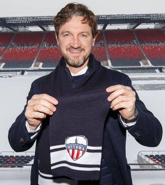 """Miguel Angel Ferrer """"Mista"""" poses with an Atletico Ottawa scarf after being named the inaugural head coach of the Canadian Premier League team in Ottawa on Tuesday, Feb. 11, 2020 in this handout photo."""