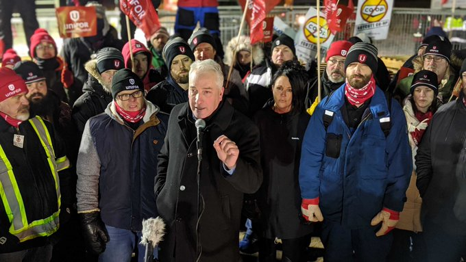 Scott Doherty, executive assistant to the national president of Unifor, speaks to a crowd outside the Co-op Refinery Complex in Regina Friday night.