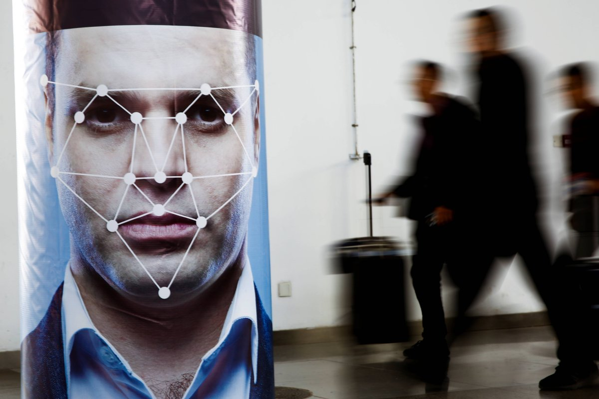 People walk past a poster simulating facial recognition software at the Security China 2018 exhibition in Beijing.
