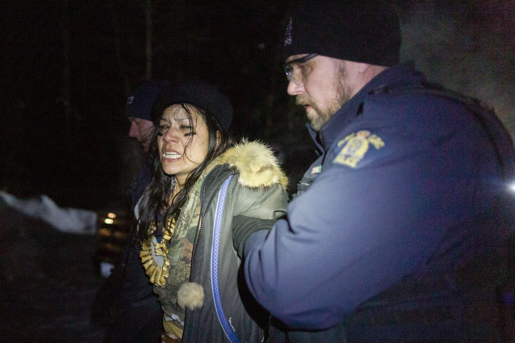 A demonstrator in Wet'suwet'en territory is detained by RCMP officers while they enforce a court injunction on Feb. 6, 2020.