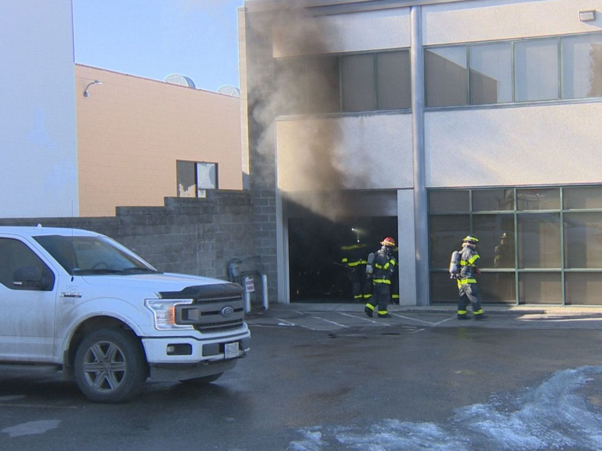 Smoke billow from a business on Moss Court in Kelowna after firefighters opened a bay door.