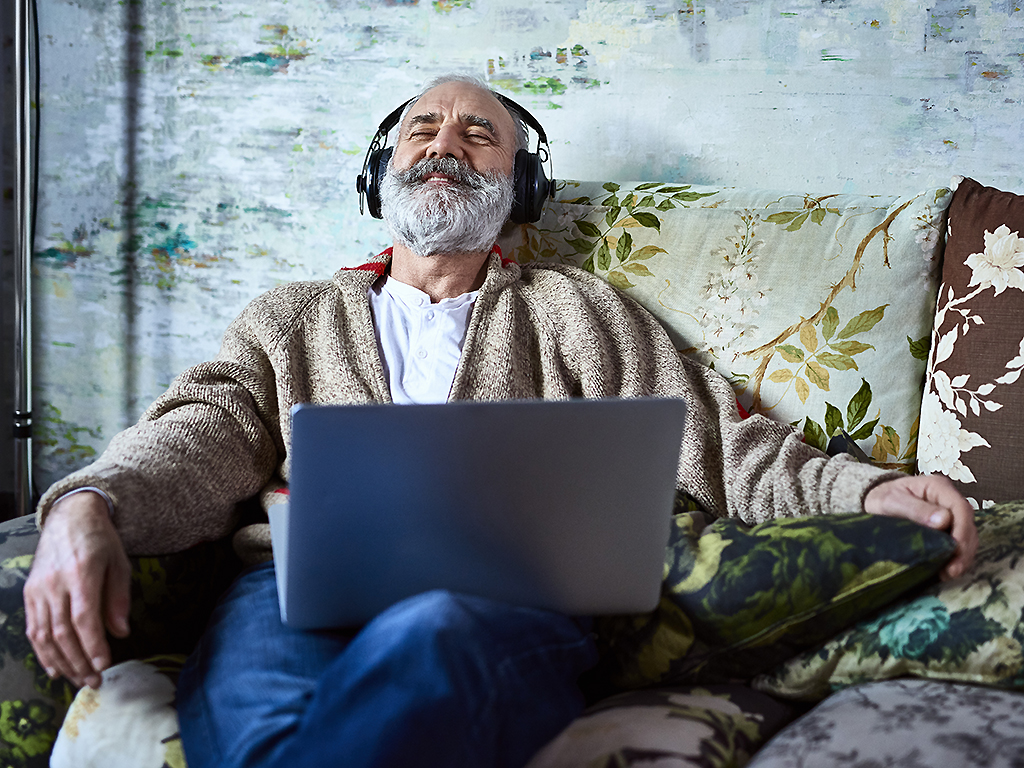 A man relaxes listening to music.