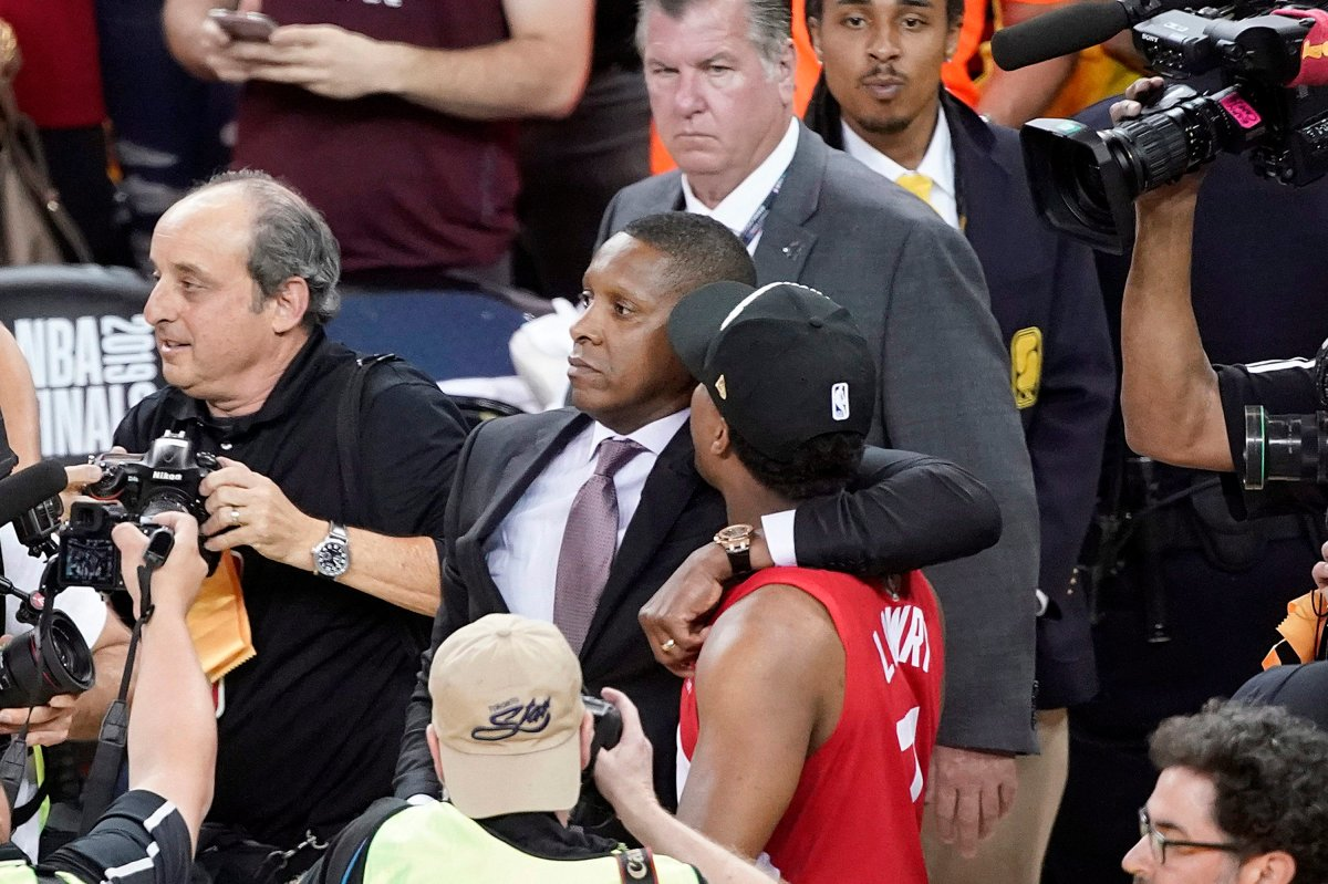 Toronto Raptors President Masai Ujiri, center left, walks with his arm around guard Kyle Lowry after the Raptors defeated the Golden State Warriors in the NBA Finals in Oakland, Calif.