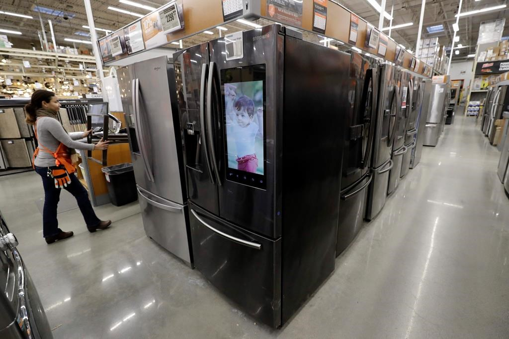 In this Jan. 27, 2020 photo a worker pushes a cart past refrigerators at a Home Depot store.