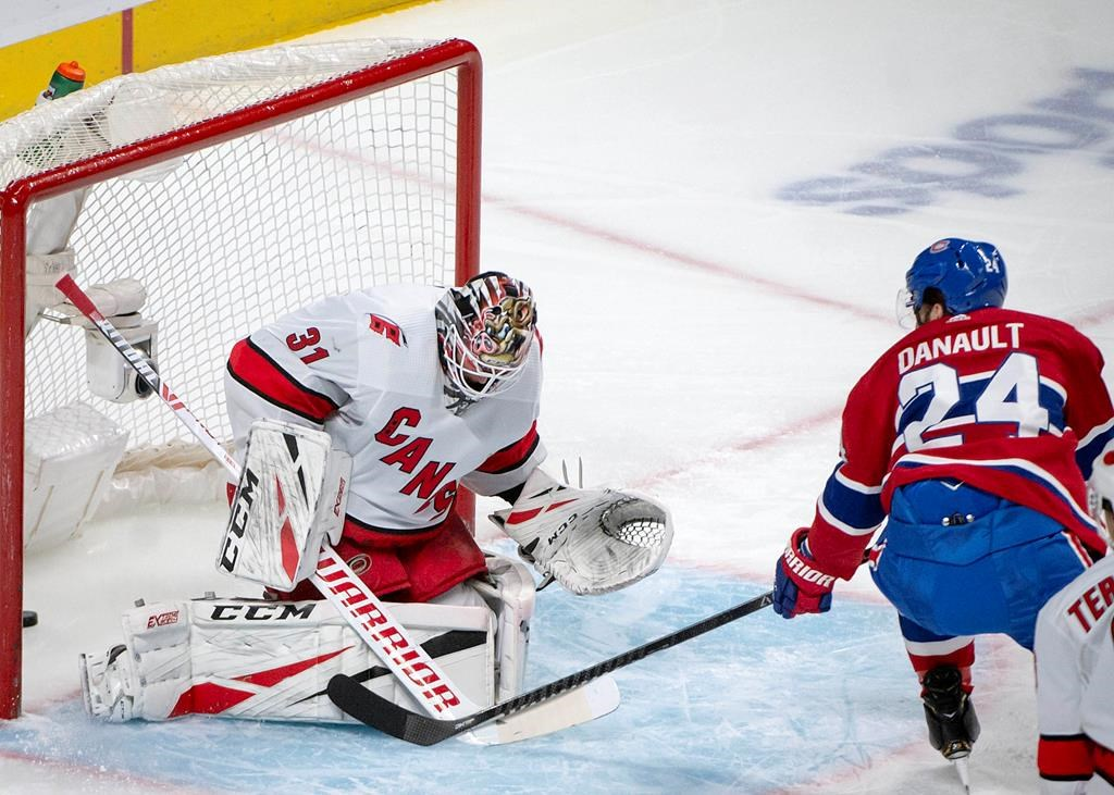 Montreal Canadiens centre Phillip Danault (24) scores on Carolina Hurricanes goaltender Anton Forsberg (31) during first-period NHL hockey action in Montreal, Saturday, Feb. 29, 2020.