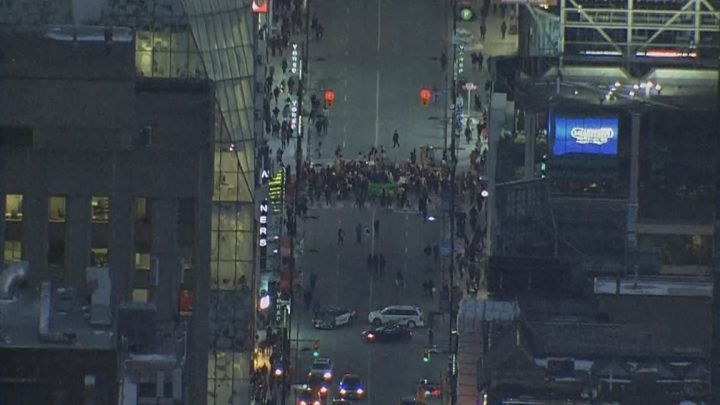 Protesters are seen blocking off the intersection of Yonge and Dundas streets in downtown Toronto Friday evening.