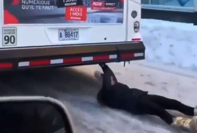 The woman is filmed gripping the bumper of the bus as it travels through downtown Montreal.
