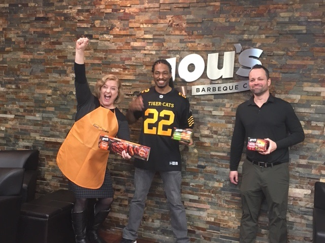 Hamilton Food Share's Celeste Taylor, Hamilton Tiger Cat defensive back Courtney Stephen and Lou's Kitchen COO Roland Love celebrate a 3,200-pound donation to local food banks.
