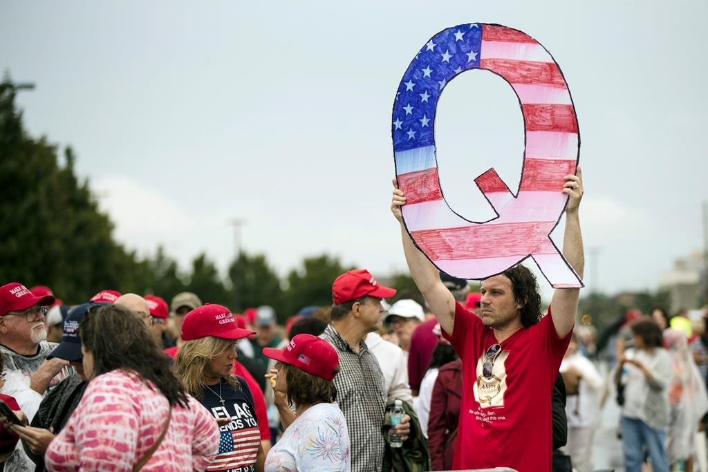 """FILE - In this Aug. 2, 2018, file photo, David Reinert holding a Q sign waits in line with others to enter a campaign rally with President Donald Trump in Wilkes-Barre, Pa. A far-right conspiracy theory forged in a dark corner of the internet is creeping into the mainstream political arena. It's called QAnon, and it centers on the baseless belief that President Donald Trump is waging a secret campaign against enemies in the """"deep state."""" (AP Photo/Matt Rourke, File)."""