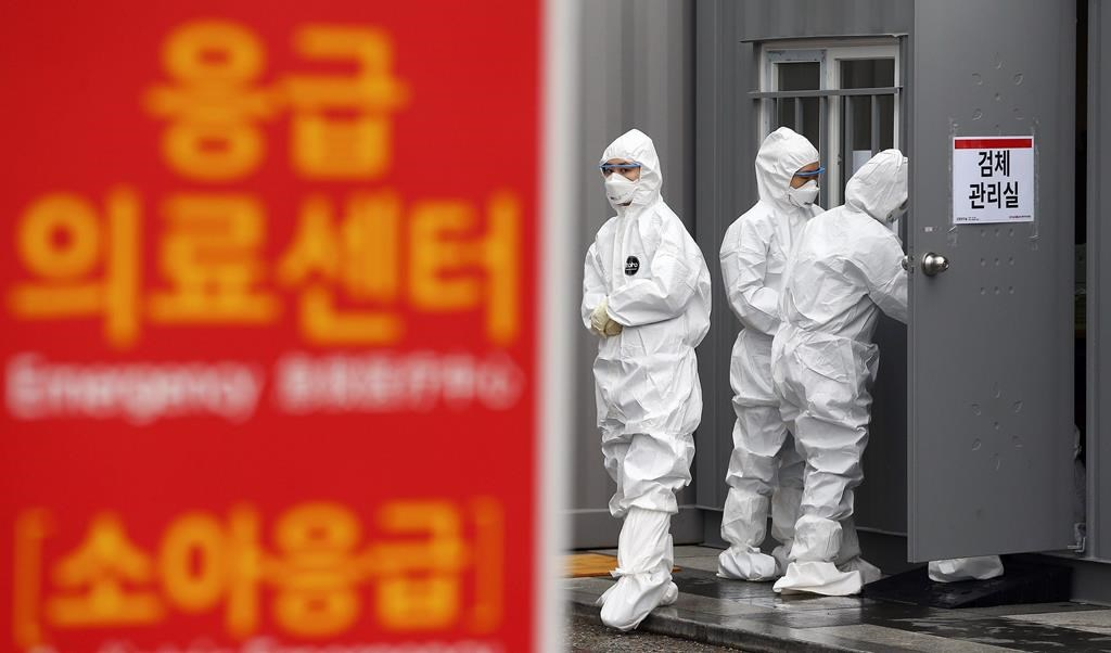 Officials wearing protective attire work to diagnose people with suspected symptoms of the new coronavirus at a hospital in Daegu, South Korea, Wednesday, Feb. 26, 2020.