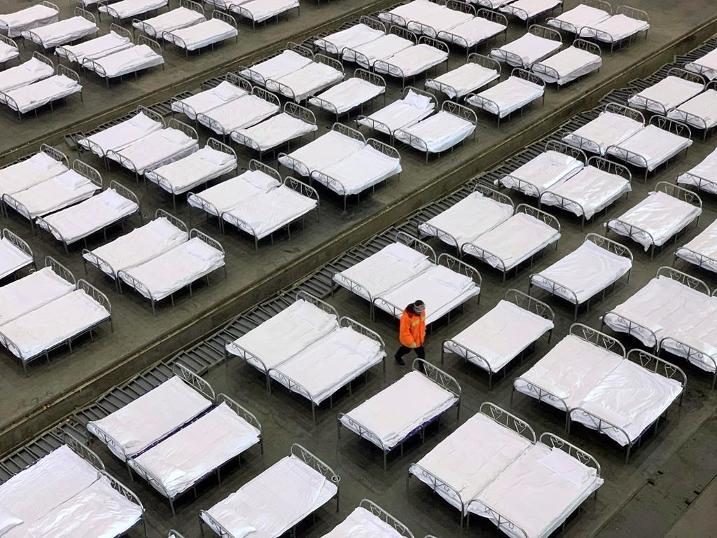 Workers arrange beds in a convention center that has been converted into a temporary hospital in Wuhan in central China's Hubei Province, Tuesday, Feb. 4, 2020.