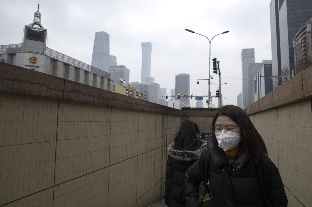 Residents walk out of a subway station near the central business district in Beijing Monday, March 9, 2020. With almost no new COVID-19 cases being reported in Beijing, workers are slowly returning to their offices with masks on and disinfectant in hand. But officials remain cautious, torn between wanting to restart the economy and fear of a resurgence of the outbreak.
