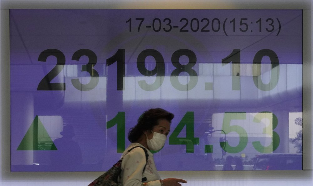 A woman wearing face mask walks past a bank electronic board showing the Hong Kong share index at Hong Kong Stock Exchange Tuesday, March. 17, 2020. Shares have reversed early losses in major Asian markets after the U.S. stock market plunged to its worst day in more than three decades.