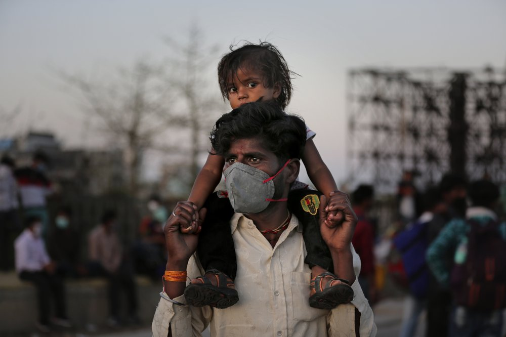 An Indian migrant worker carries a child on his shoulders as they wait for transportation to their village following a lockdown amid concern over spread of coronavirus in New Delhi, India, Saturday, March 28, 2020. Authorities sent a fleet of buses to the outskirts of India's capital on Saturday to meet an exodus of migrant workers desperately trying to reach their home villages during the world's largest coronavirus lockdown. Thousands of people, mostly young male day laborers but also families, fled their New Delhi homes after Prime Minister Narendra Modi announced a 21-day lockdown that began on Wednesday and effectively put millions of Indians who live off daily earnings out of work.