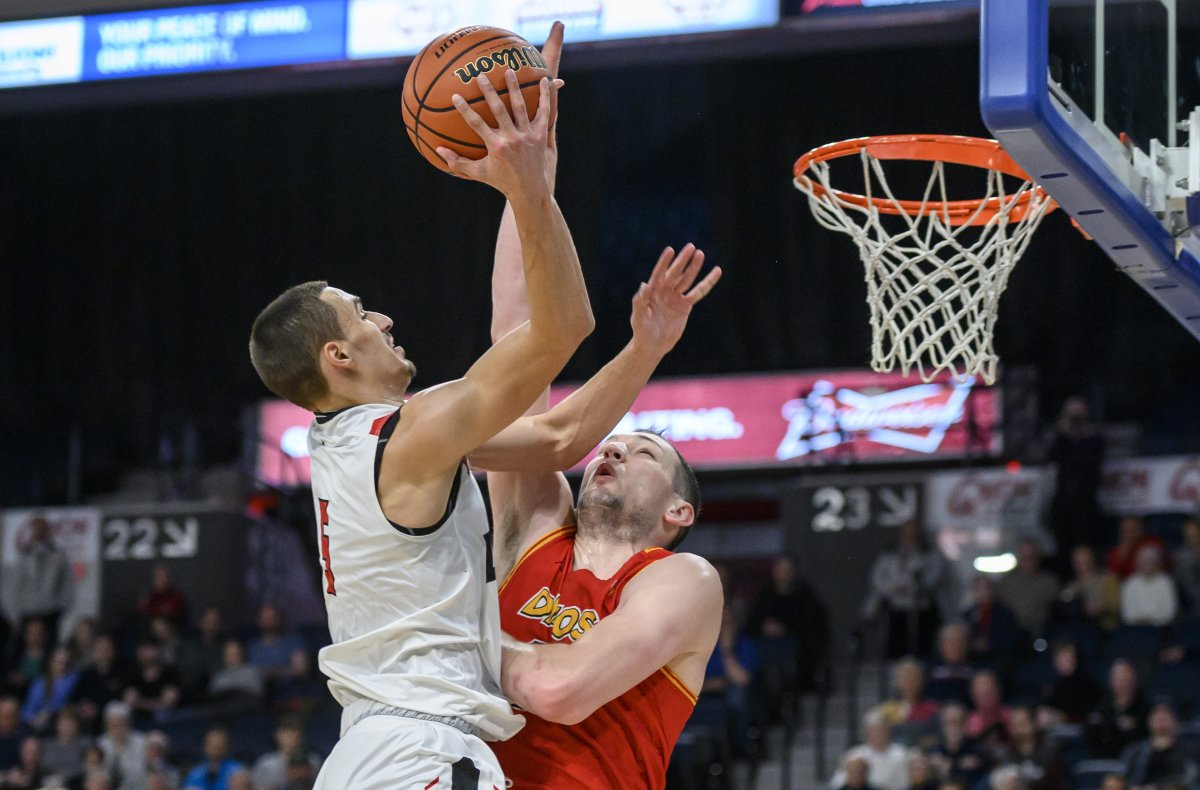 Carleton Ravens' Isiah Osborne, left, scores over University of Calgary Dinos' Brett Layton during the second half of the gold medal final in the USports men's basketball national championship in Halifax on Sunday, March 10, 2019.