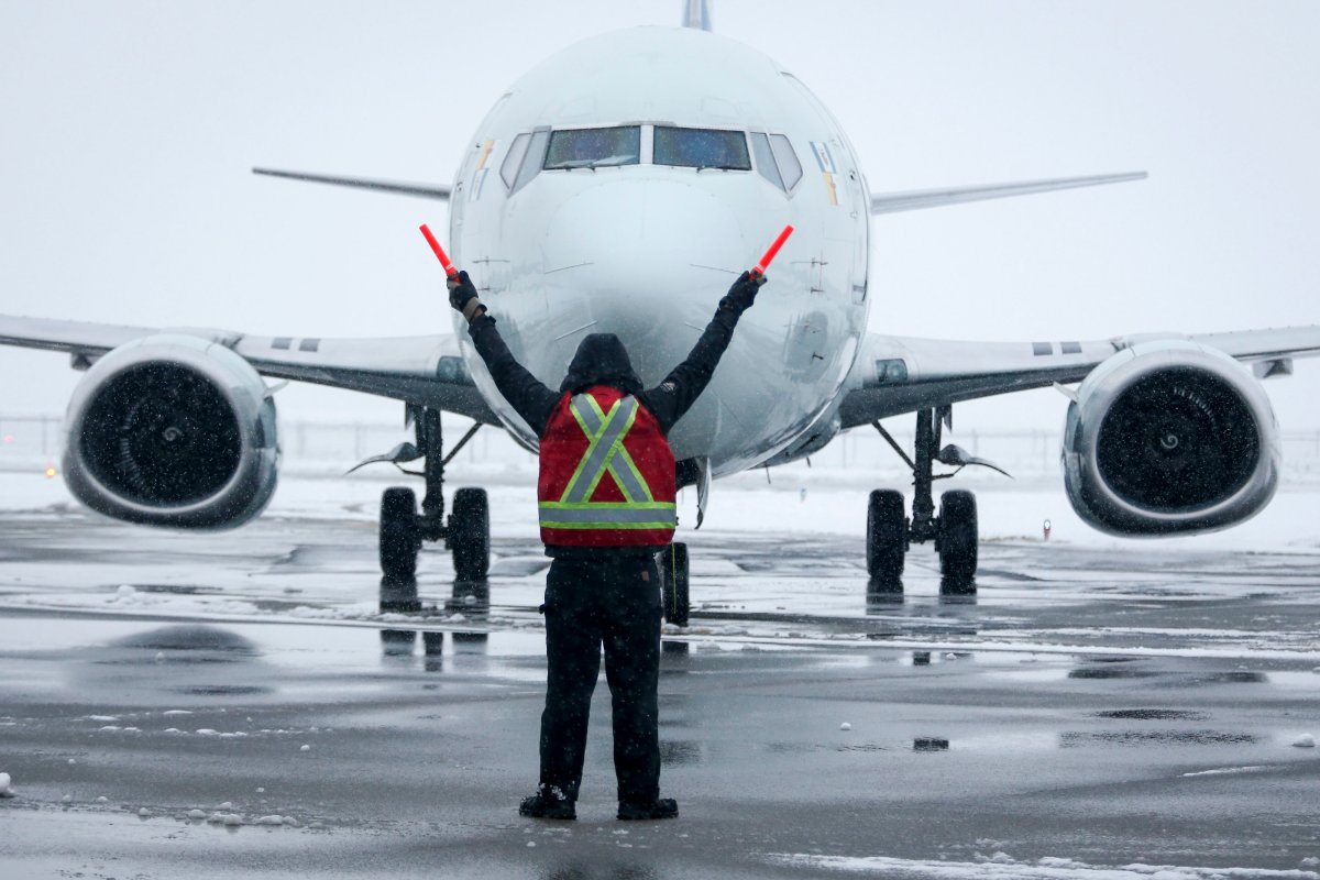 A ground crew member guides a plane into position at an airport in Calgary, Alta., Tuesday, Nov. 19, 2019.