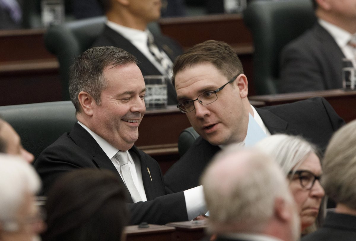 Alberta Premier Jason Kenny Jason Nixon Minister of Environment and Parks chat before the speech from the throne is delivered in Edmonton Alta, on Tuesday May 21, 2019.