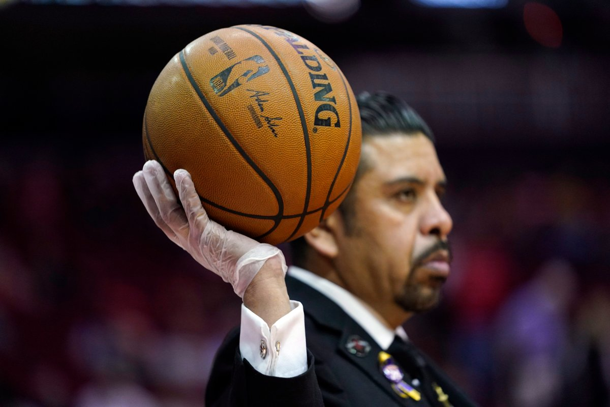 Security guard David Castillo wears gloves while holding a basketball during halftime of an NBA basketball game between the Los Angeles Clippers and Houston Rockets Thursday, March 5, 2020, in Houston.