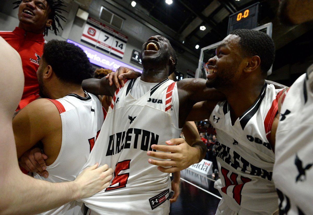 Carleton University Ravens guard Munis Tutu (5) celebrates with forward Lloyd Pandi (41) celebrate their team's win over the Dalhousie Tigers in the men's championship final basketball game of the U Sports Final 8 Championships, in Ottawa, on Sunday, March 8, 2020.