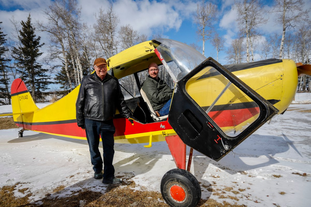 Richard Reid, left, and his son David Reid, who are both farmers and pilots, look over the plane that Richard purchased as a 17 year-old and which his son David is now restoring at their farm near Cremona, Alta., Wednesday, March 4, 2020.