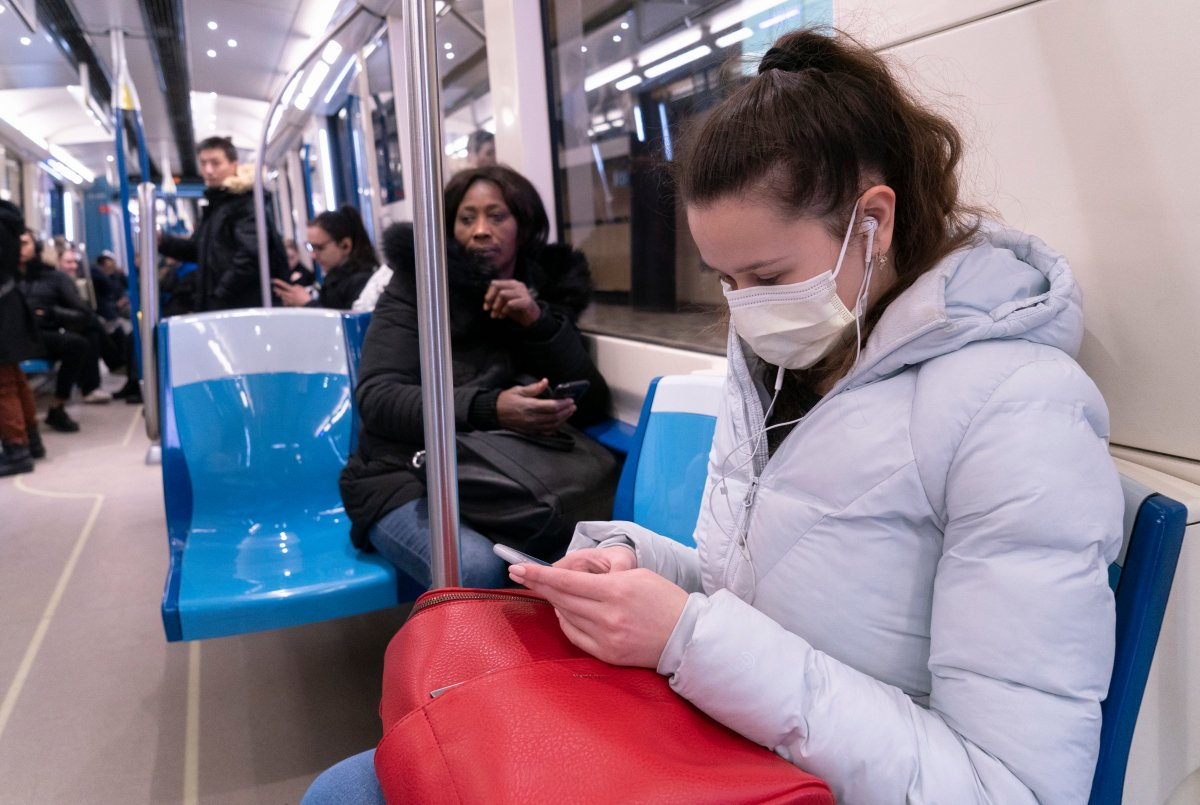 A commuter wears a protective mask as she rides the Metro in Montreal on Friday, March 13, 2020.