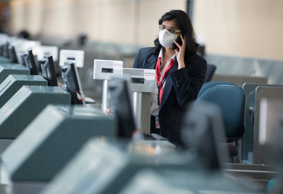 An airline employee is seen at Vancouver International Airport in Richmond, B.C. Friday, March 13, 2020.