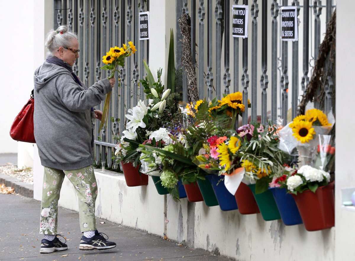 A woman prepares to lay flowers outside the Al Noor mosque in Christchurch, New Zealand, Sunday, March 15, 2020.