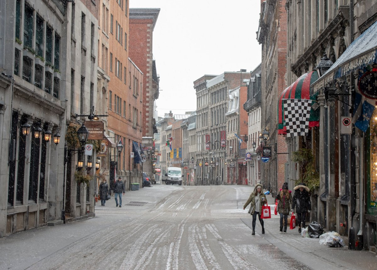 Tourists walk along the street as Old Montreal is nearly deserted, Tuesday, March 17, 2020 in Montreal. Quebec premier promises aid for hotels feeling impact of pandemic on tourism.