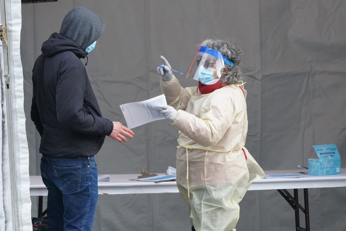 Healthcare worker directing a person for further testing at the COVID-19 outdoor emergency clinic in Montreal, Que., Monday, March 23, 2020.