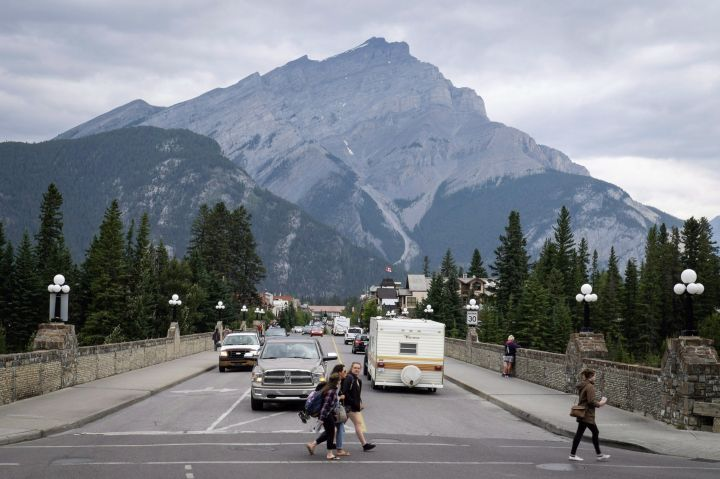 People walk across a street in Banff, Alta., in Banff National Park, Friday, July 21, 2017.