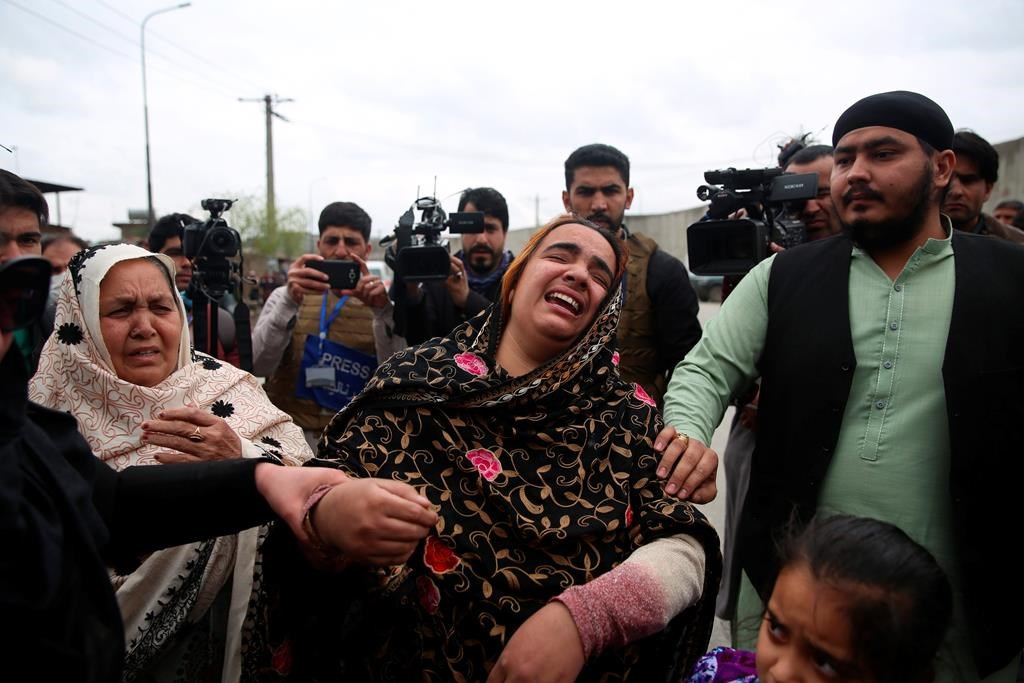 Family members cry after an attack in Kabul, Afghanistan, Wednesday, March 25, 2020. Gunmen stormed a religious gathering of Afghanistan's minority Sikhs in their place of worship in the heart of the Afghan capital's old city on Wednesday, a minority Sikh parliamentarian said.