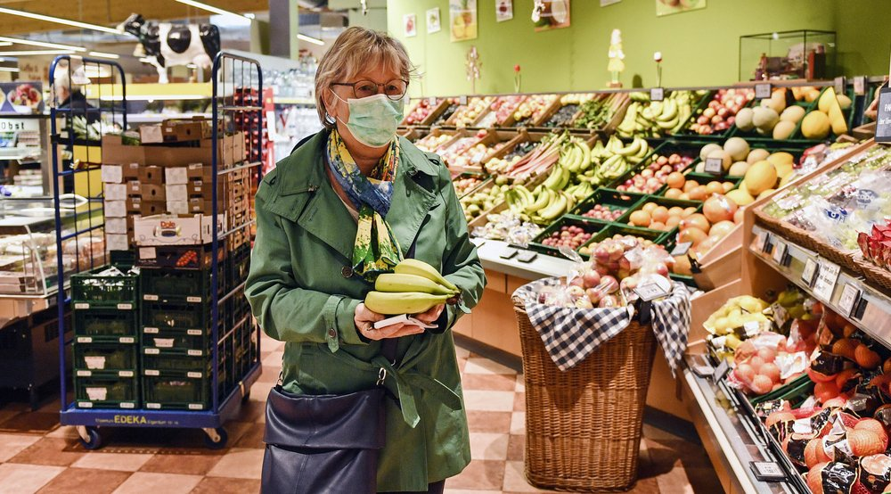 A woman buys fruits at a supermarket in Bergisch Gladbach that is open in the morning only for elderly people from 65 years to minimize their risk of infection due to the coronavirus outbreak in Germany, Friday, March 20, 2020. For most people, the new coronavirus causes only mild or moderate symptoms, such as fever and cough. For some, especially older adults and people with existing health problems, it can cause more severe illness, including pneumonia. (AP Photo/Martin Meissner) .