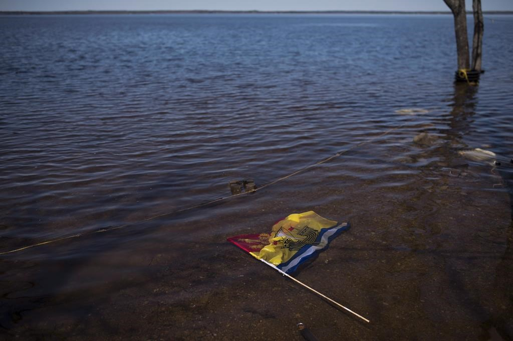 A New Brunswick flag floats in floodwater from the Saint John River in Waterborough, N.B., on May 13, 2018.
