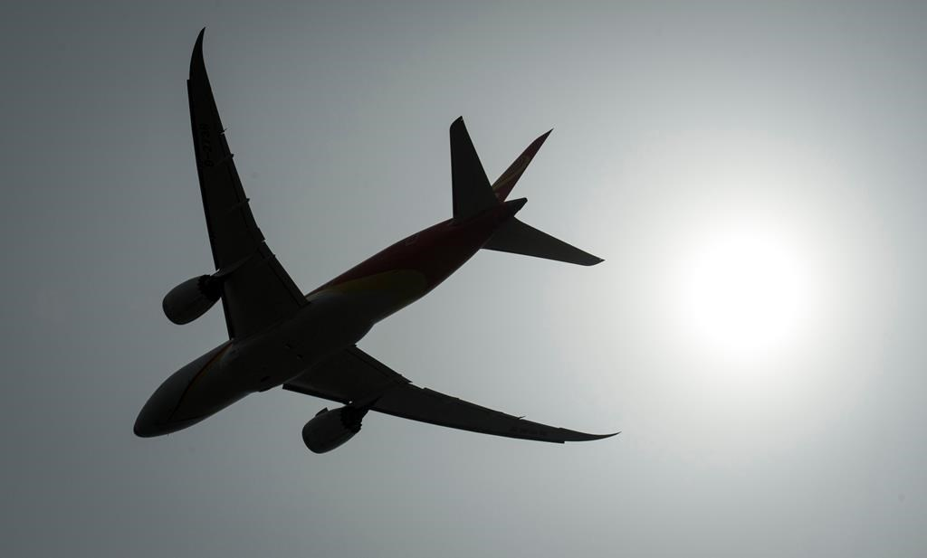 A plane is silhouetted as it takes off from Vancouver International Airport in Richmond, B.C., on May 13, 2019.