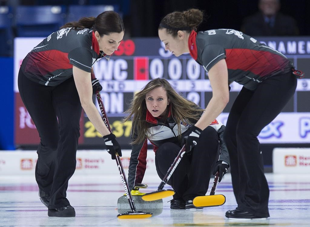 Ontario skip Rachel Homan delivers a rock as lead Lisa Weagle, left, and second Joanne Courtney sweep in championship pool action against the Wild Card team at the Scotties Tournament of Hearts at Centre 200 in Sydney, N.S. on Thursday, Feb. 21, 2019. Weagle was shocked to receive word this week that Team Homan would no longer be needing her services. THE CANADIAN PRESS/Andrew Vaughan.